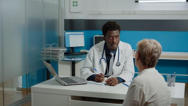 Médico com experiência em saúde, consultando uma mulher idosa