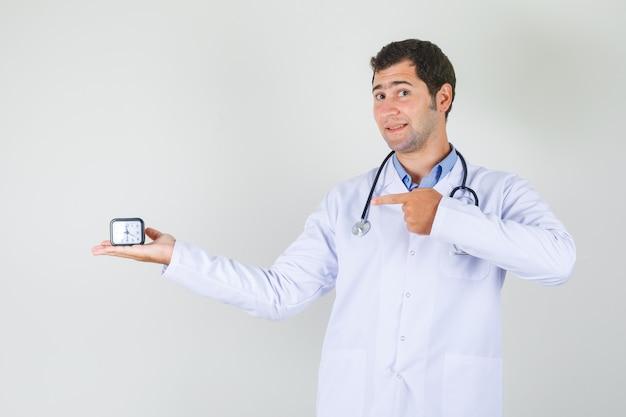 Médico com jaleco branco apontando o dedo para o relógio e parecendo alegre