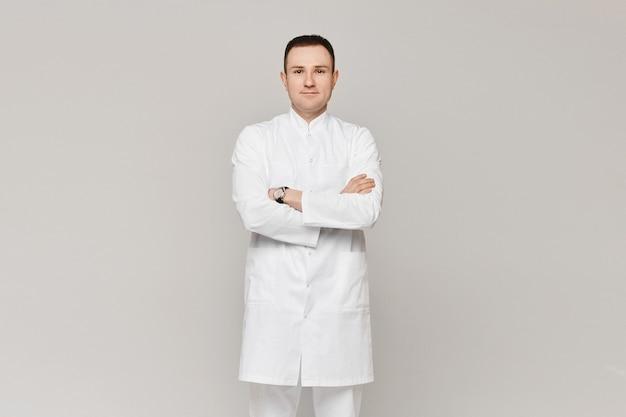 Médico com jaleco branco em pé com os braços cruzados