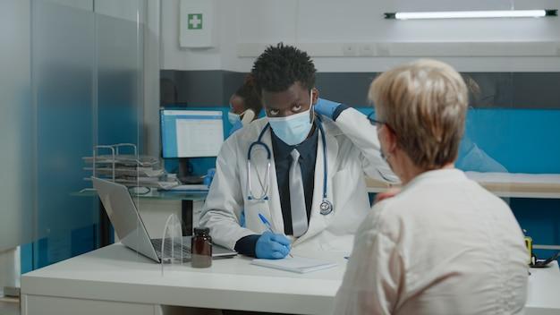 Médico com jaleco branco sentado à mesa enquanto fala com uma mulher mais velha