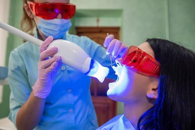 Médico com lâmpada e espelho tratando os dentes dos pacientes de perto