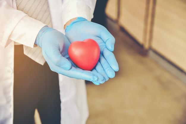 Médico com luvas de borracha azul, segurando um coração vermelho.