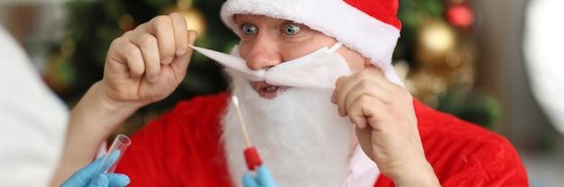 Médico com luvas de borracha tirando um cotonete nasal de pcr para o papai noel perto da árvore de natal
