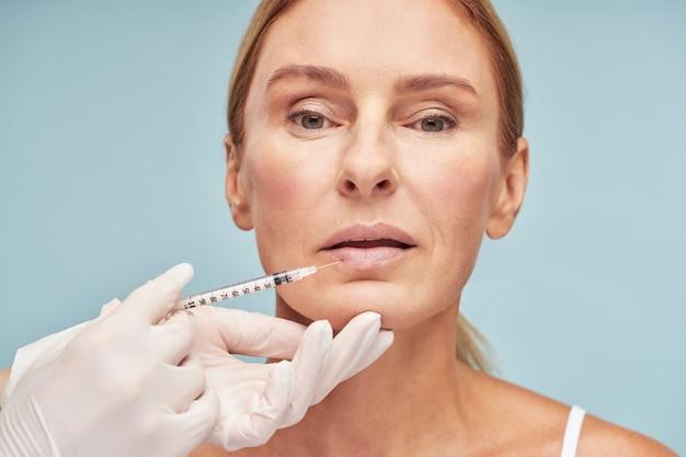 Médico com luvas de proteção fazendo procedimento de aumento dos lábios