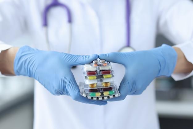 Médico com luvas detém medicamentos. conceito de uso não controlado de medicamentos