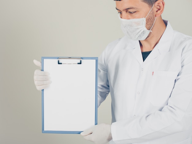 Médico com luvas olhando e segurando o suporte de papel na vertical. vista lateral.
