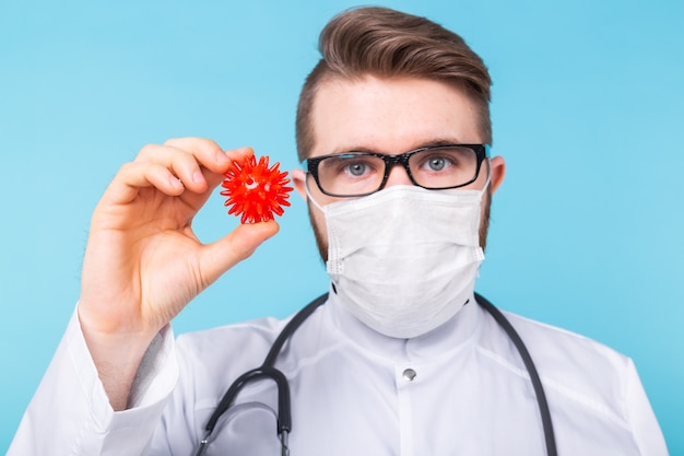 Médico com máscara contra gripe e luvas de proteção segura um modelo de coronavírus