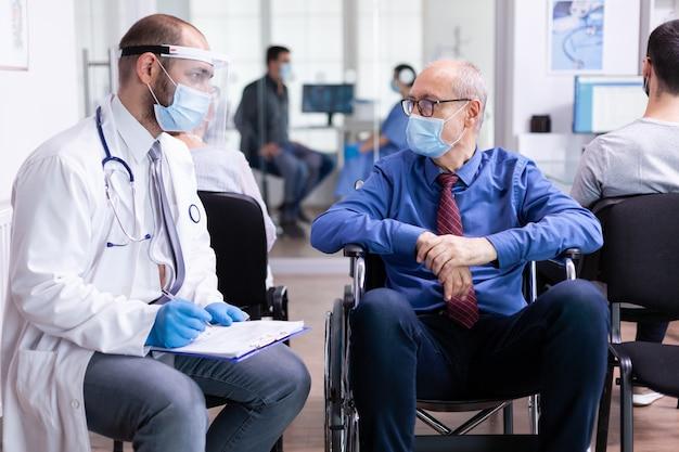 Médico com máscara facial e estetoscópio consultando um homem idoso com deficiência na sala de espera do hospital
