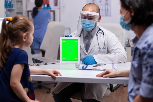 Médico com máscara facial e viseira usando tablet pc de tela verde no consultório durante a pandemia de coronavírus