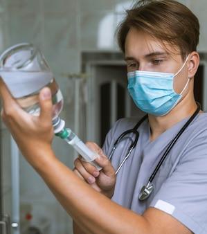Médico com máscara médica enchendo seringa com remédio Foto Premium