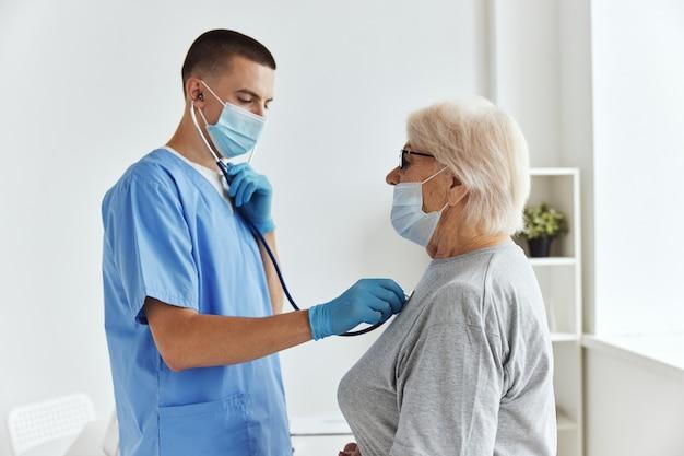 Médico com máscara médica examina o tratamento de um paciente
