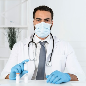 Médico com máscara médica segurando um recipiente de vacina