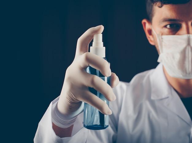 Médico com máscara segurando spray médico na mão. vista lateral.
