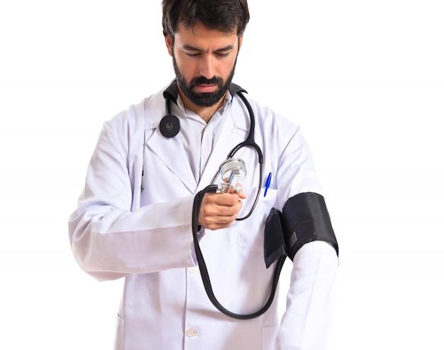 Médico com monitor de pressão sanguínea sobre fundo branco