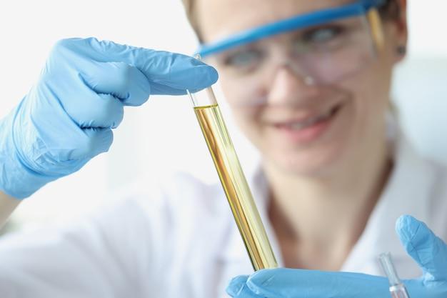 Médico com óculos de segurança segurando um tubo de ensaio com um líquido amarelo em close do laboratório