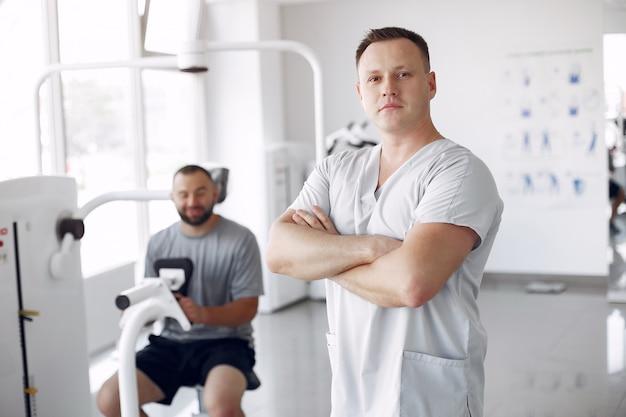 Médico com paciente em clínica de fisioterapia