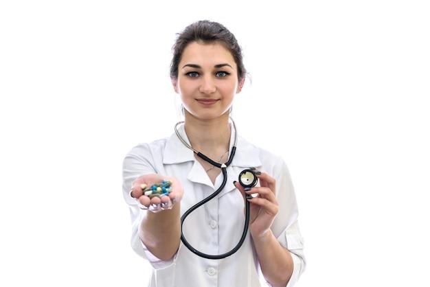 Médico com pílulas coloridas na palma da mão isoladas na parede branca