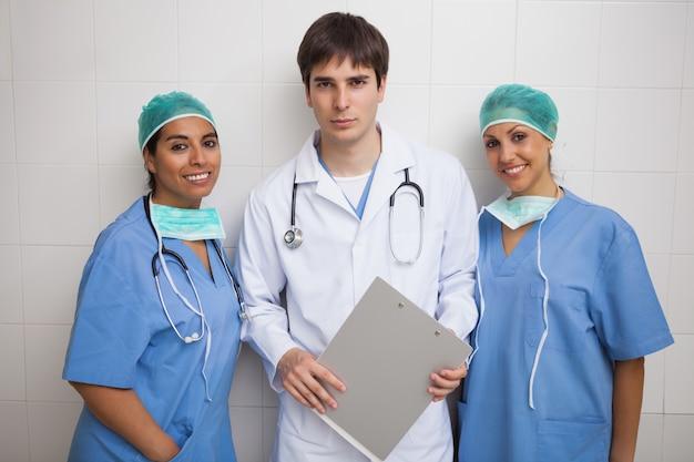 Médico com prancheta fica entre duas enfermeiras