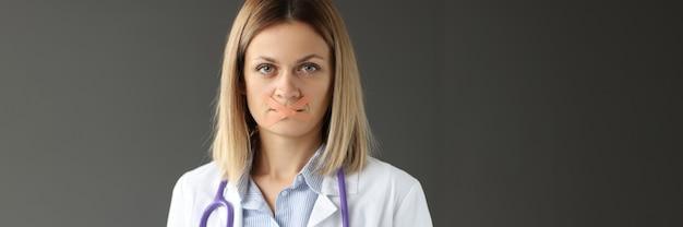 Médico com prancheta nas mãos e fita adesiva selada sobre a boca sigilo médico e