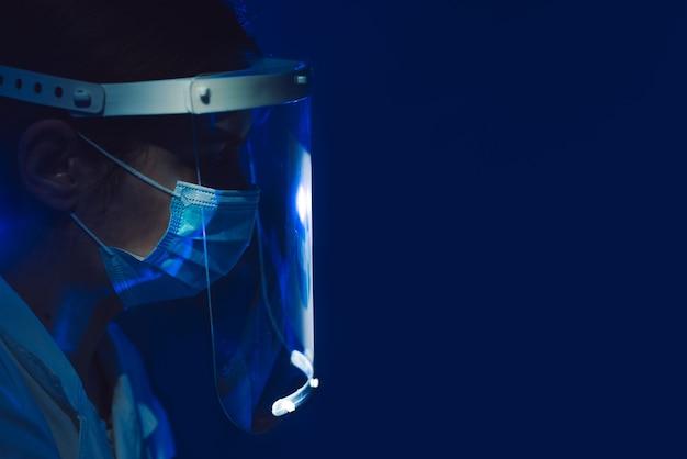 Médico com protetor facial e máscara em fundo azul escuro