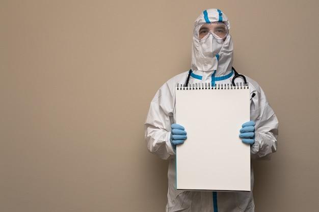 Médico com roupa de proteção médica segurando um grande bloco de notas