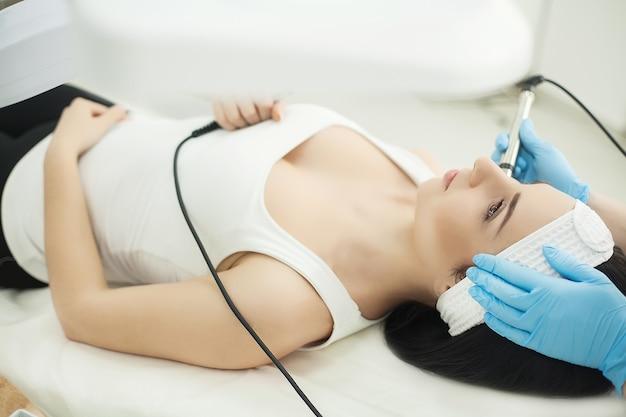 Médico com scraber ultra-sônico, procedimento de limpeza ultra-sônica do rosto