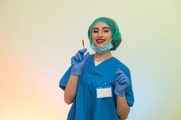 Médico com seringa e tubo de ensaio vermelho posando no hospital