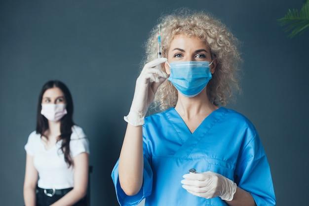 Médico com seringa na mão e um paciente perto de uma jovem recebendo o conceito de vacinação