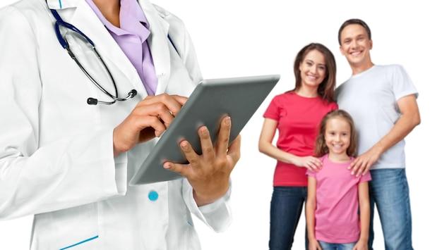 Médico com tablet pc e família feliz no fundo, conceito de saúde,