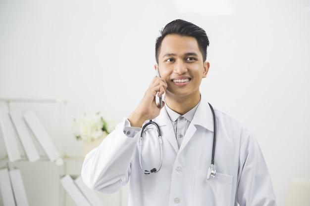 Médico com telefonema no consultório médico