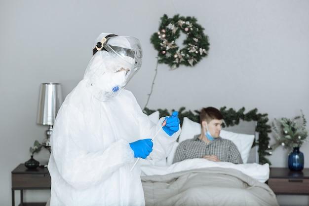 Médico com traje de proteção de epi se preparando faz um teste de pcr para coronavírus covid-19 em um paciente com sinais do vírus