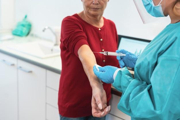 Médico com traje de proteção e luvas, dando a um paciente idoso uma vacina para a cura