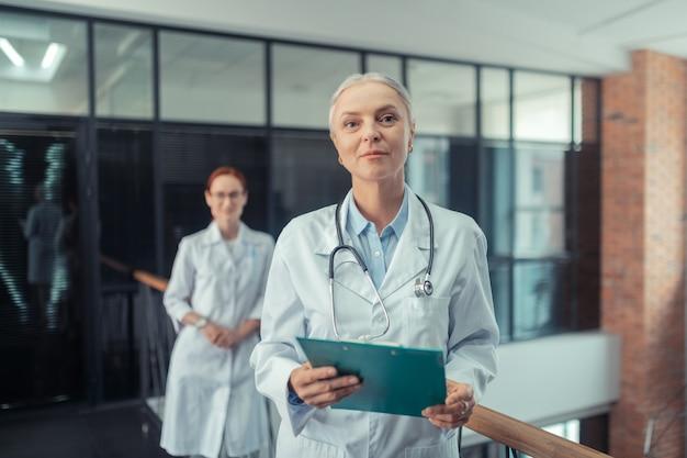 Médico com um estetoscópio. calma médica sênior com um estetoscópio no pescoço, de pé no corredor ao lado de sua jovem colega