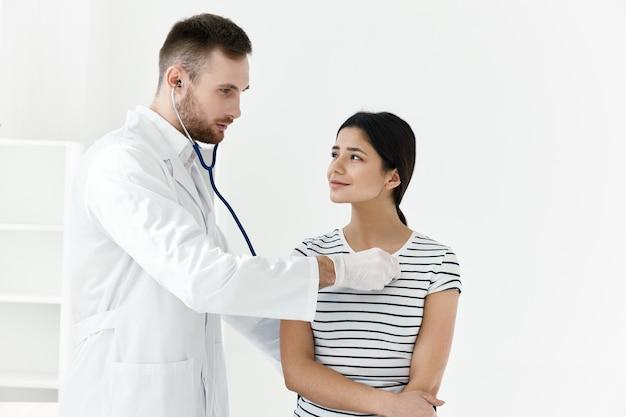 Médico com um estetoscópio de jaleco branco, exame de um paciente em um hospital