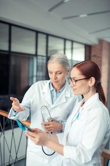 Médico com um estetoscópio. mulher sênior com um estetoscópio olhando para a tela do tablet ao lado de seu colega