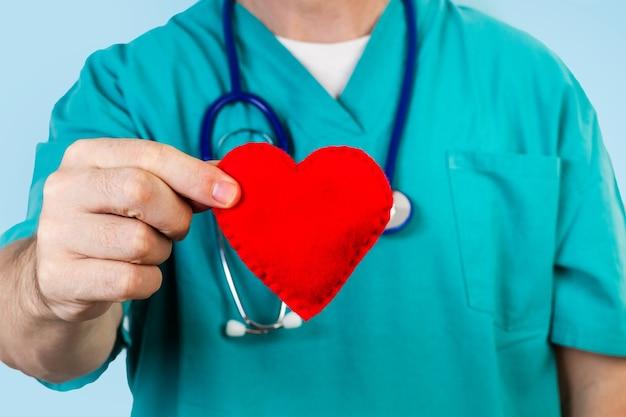 Médico com um estetoscópio segurando um coração de tecido vermelho em uma visão de perto