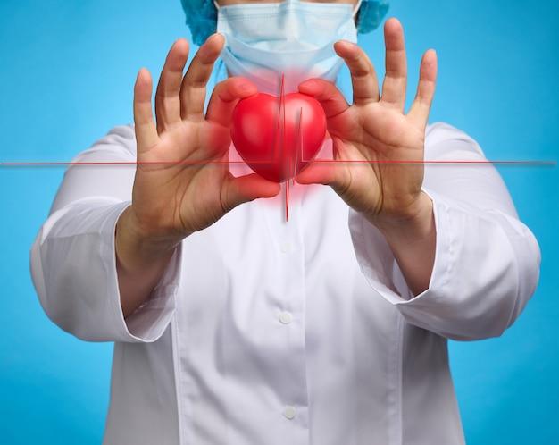 Médico com um jaleco branco segurando um coração vermelho. conceito de doença cardiovascular, diagnóstico precoce. fundo azul