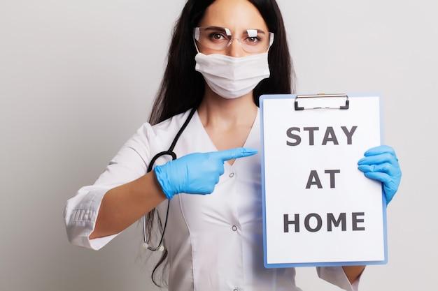 Médico com um papel com ficar em casa segurando na mão