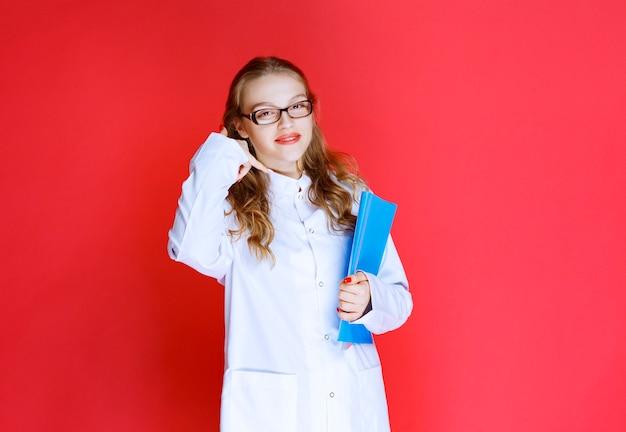 Médico com uma pasta azul pedindo para entrar em contato com ela.