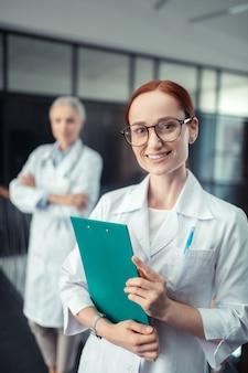 Médico com uma prancheta. médica feliz com uma prancheta em pé no corredor ao lado de sua colega, olhando para a frente dela