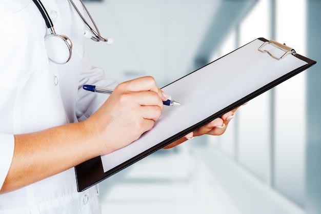 Médico com uma revista clínica de clientes e endoscópio.