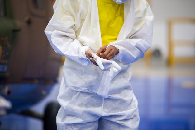 Médico com uniforme de epi calçando luvas médicas