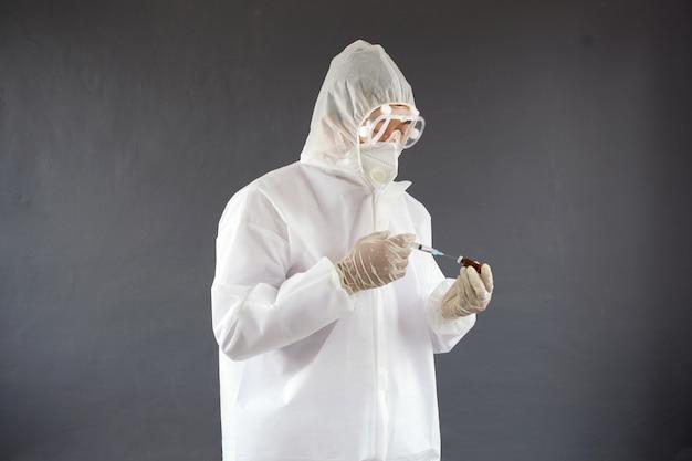 Médico com uniforme de epp usando máscara facial de proteção contra vírus segurando um frasco de vacina líquida de medicamento