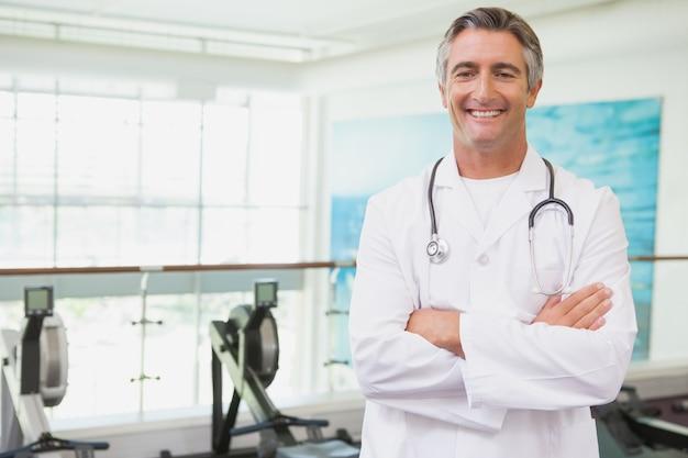 Médico confiante em pé no estúdio de fitness
