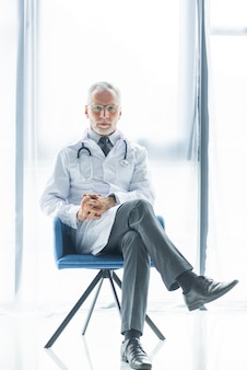 Médico confiante sentado na cadeira