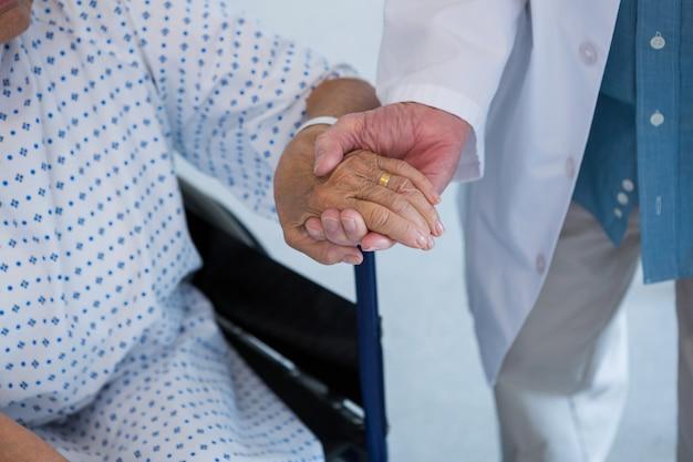 Médico consolando paciente idoso em cadeira de rodas no hospital