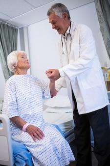 Médico consolando paciente sênior na enfermaria