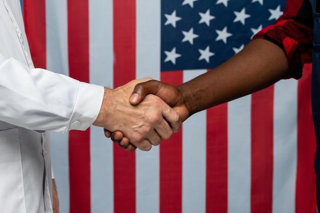 Médico contemporâneo de jaleco branco e jovem reparador africano apertando as mãos contra a bandeira das estrelas e listras