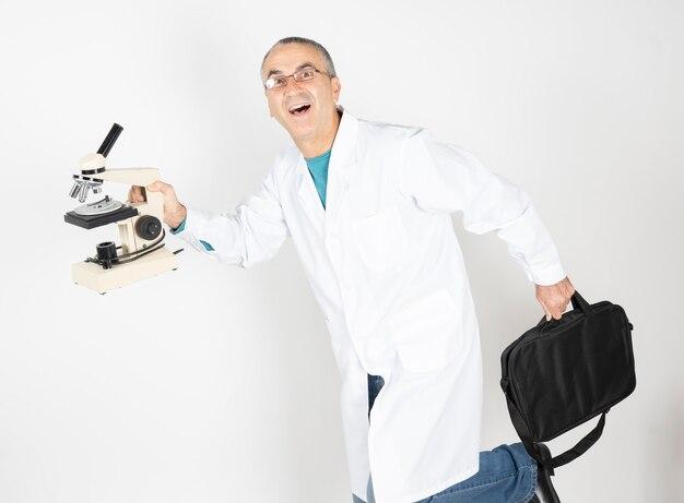 Médico correndo com maleta e gesto engraçado de microscópio em fundo branco