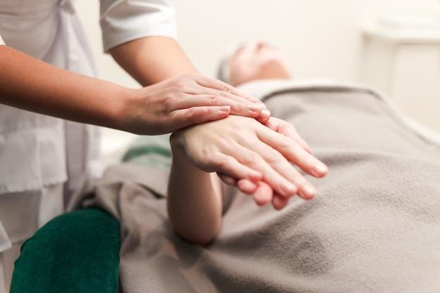 Médico cosmetologista massageia as mãos de seu paciente. cliente de um salão de beleza desfruta de uma massagem nas mãos